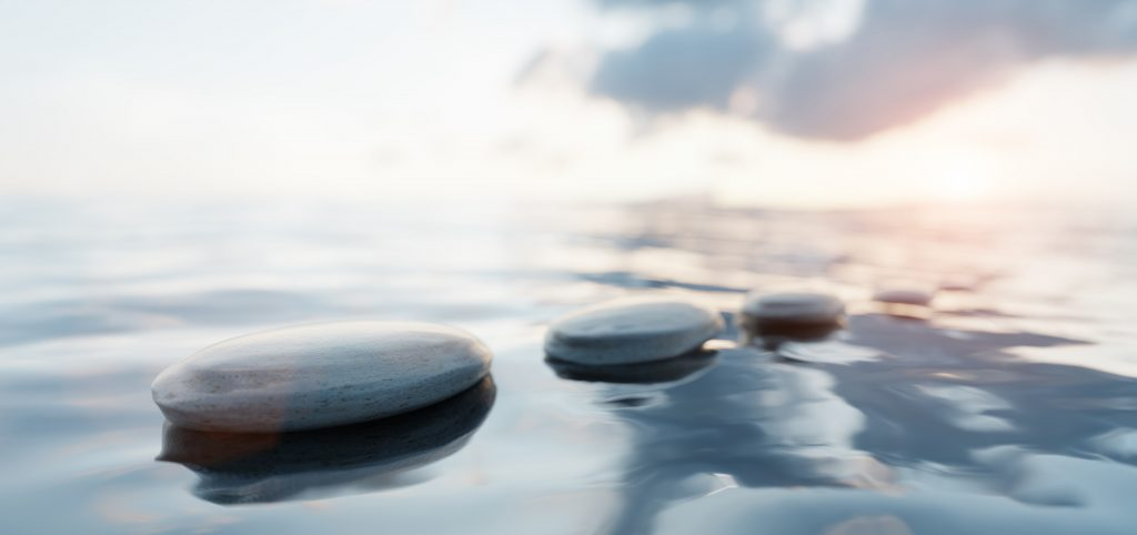 Zen stones on calm water to soothe the mind.